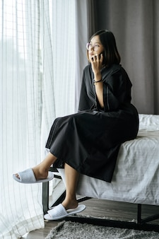 Woman wearing a white shirt, sitting on the bed and talking on the phone.