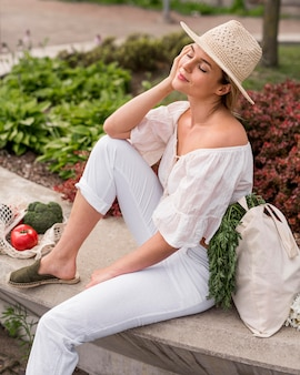 Woman wearing white sitting next to veggies