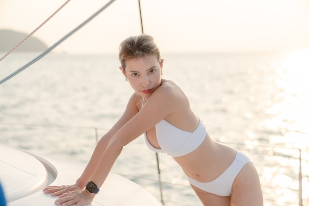 Woman wearing white swimsuit relax on sailing yacht, romantic sunset.