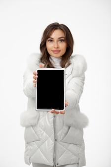 Женщина в зимней одежде и держит планшет