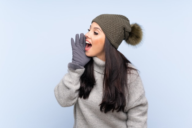 Woman wearing winter clothes over isolated wall