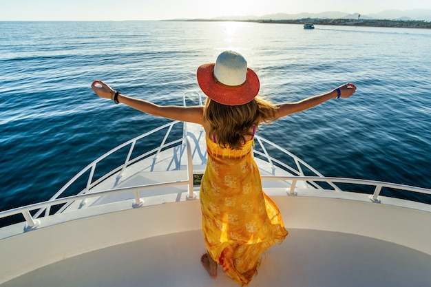 Woman wearing yellow dress and straw hat standing with raised hands on white yacht deck