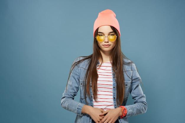 黄色いメガネをかけている女性ピンクの帽子のファッションは、モダンな服をポーズします。高品質の写真