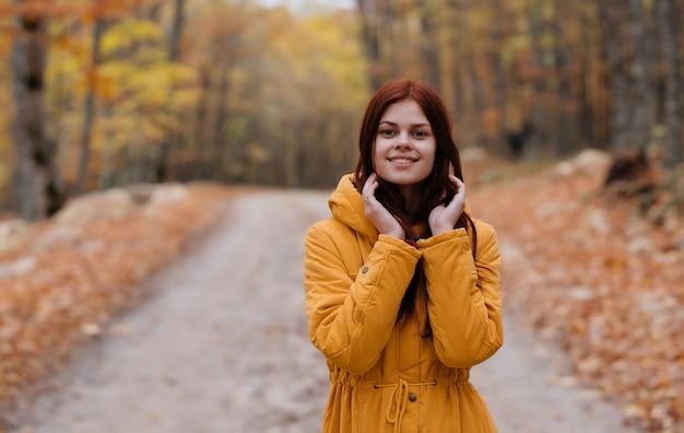 노란색 재킷을 입고 여자 가을 숲 도보 여행 자연. 고품질 사진