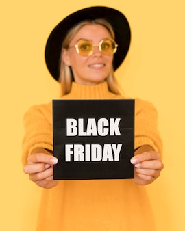 Woman wearing yellow shirt holding black friday squared card
