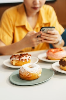 Woman wearing yellow shirt taking photos of strawberry pink, chocolate, sugar glazed and bacon, cheese donut.