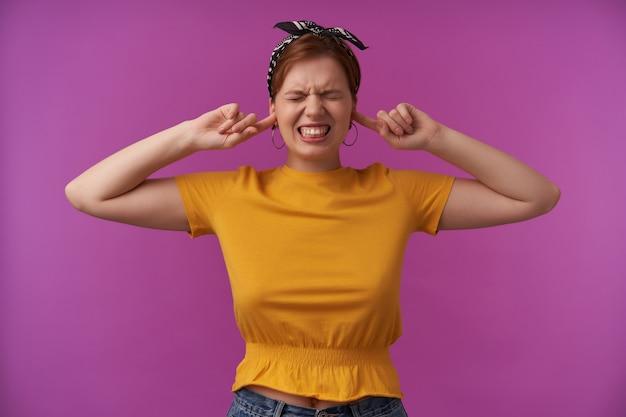 黄色のスタイリッシュなtシャツと黒のバンダナの感情を身に着けている女性怒り怒り狂ったストレスの多い指が耳に触れる目を閉じた怒った顔が紫色の壁にポーズをとる