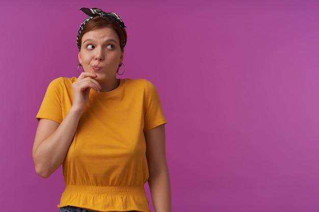 黄色のtシャツと黒いバンダナの感情を身に着けている女性は、紫色の壁に恥ずかしがり屋のポーズをとって、混乱して驚いて驚いて驚いて気配りのある表情を脇に置いて強調しました