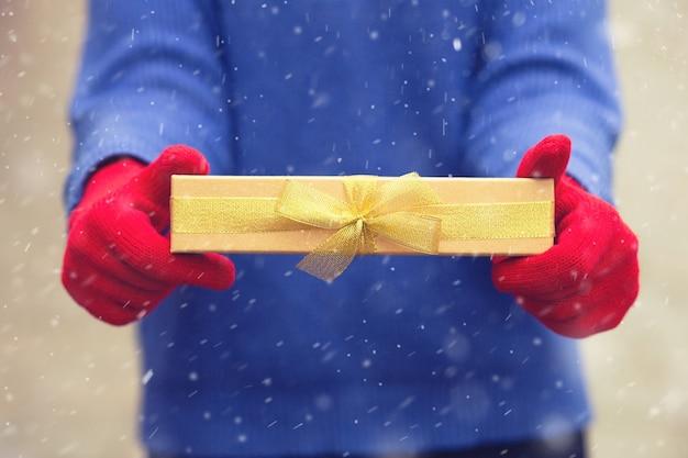 女性は降雪時に弓でギフトボックスを保持している青いセーターと赤い冬の手袋を着用します