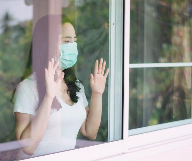 여자는 마스크를 쓰고 코로나 바이러스의 확산을 막기 위해 집에 머물러 있습니다