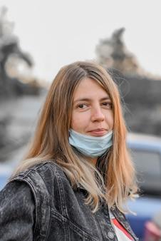 Женщина носит медицинскую маску, потому что загрязнение воздуха или вирус - эпидемия в городе.