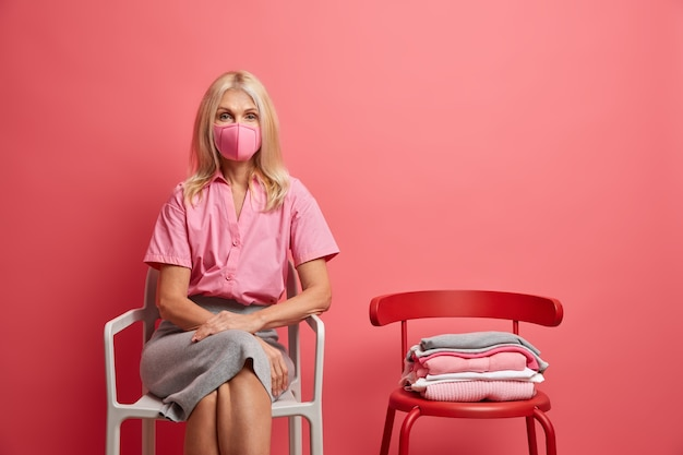 Woman wears anti virus protection mask stays at home during quarantine being on self isolation tries to stop epidemic disease sits at chair isolated on pink