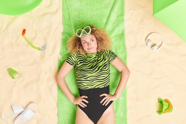 Woman wears bikini snorkeling mask on forehead looks away lies on green towel thinks about something pleasant enjoys sunbathing.