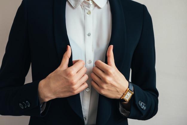 Woman wears a business suit jacket. in her hand wristwatch