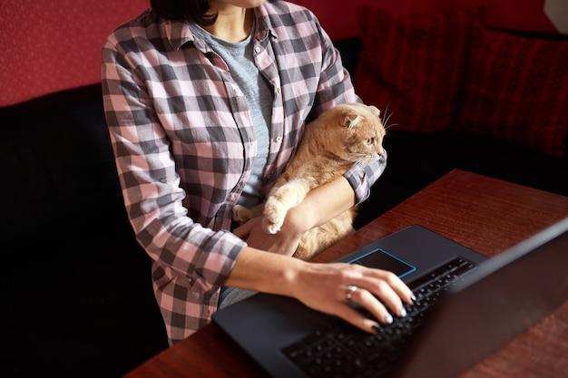 Женщина носит удобный стиль, работает с черным блокнотом и держит кошку