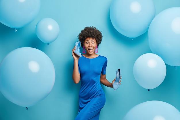 여자 착용 드레스 파란색에 파티 포즈에 대한 높은 굽 신발 드레스를 보유
