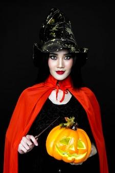 女性はハロウィーンの衣装と杖とカボチャを保持しています。