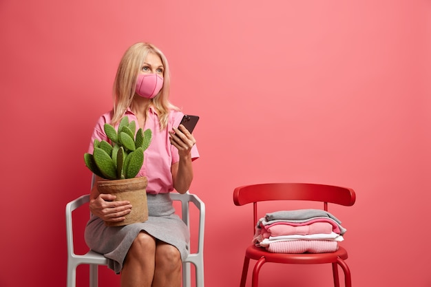 Woman wears hygienic mask to prevent infection coronavirus uses smartphone for chatting holds pot of cactus poses on chair isolated on pink