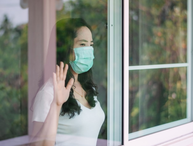 Woman wears a mask and stays at home to prevent the spread of the coronavirus