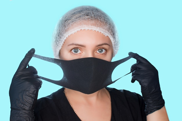 Woman wears a medical mask. girl in protective gloves and a cap