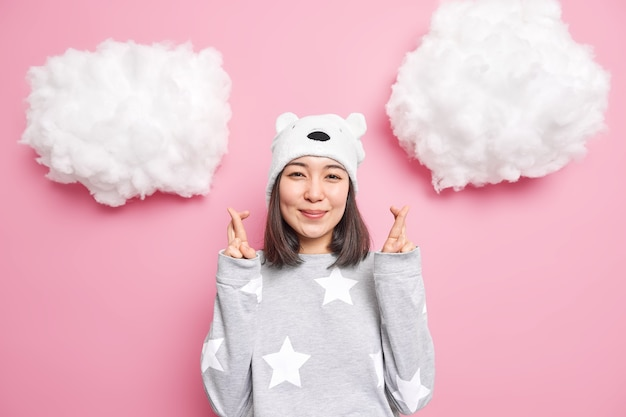 Woman wears pajama bear hat crosses fingers waits for good news makes wish or prays anticipates something happen isolated on pink