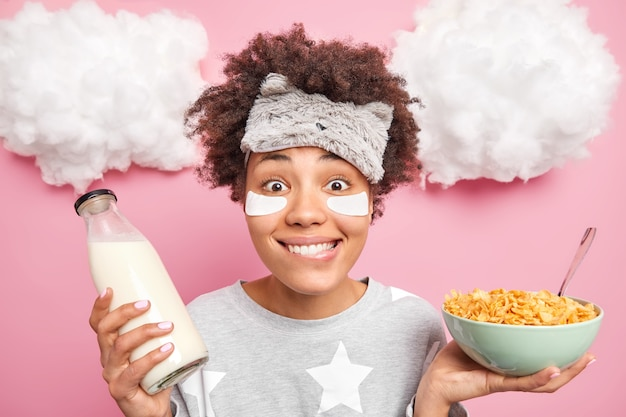 Woman wears pajama sleepmask patches under eyes holds bowl of cereals and milk has nutrient breakfast poses indoor
