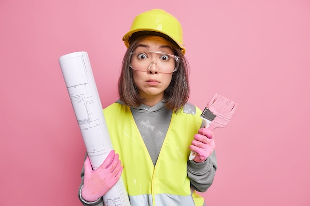 Woman wears protective helmet glasses and gloves going to paint something busy with house repairing holds blueprint