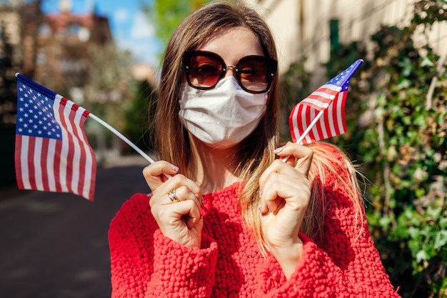 Woman wears protective mask outdoors celebrates usa independence day with flags during coronavirus covid-19