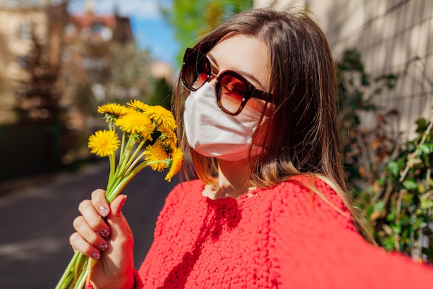 Woman wears protective mask outdoors during coronavirus covid-19 pandemic smells flowers.