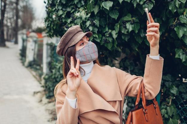コロナウイルスcovid-19パンデミックの最中、屋外で女性が再利用可能なマスクを着用しています。空の通りにselfieを取っている女の子。おげんきで