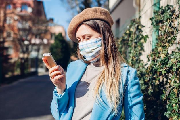 コロナウイルスcovid-19パンデミックの最中、屋外で女性が再利用可能なマスクを着用しています。女性が空の通りに電話を使用しています。