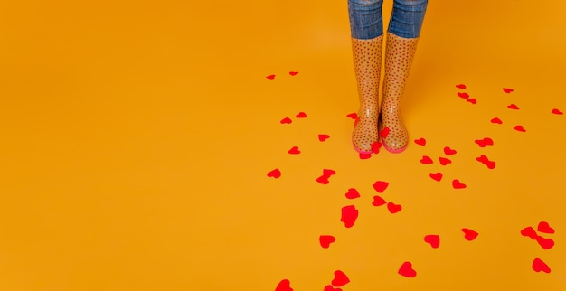 Woman wears rubber boots standing on the floor covering with many hearts. studio shot of shapely lady in yellow gumshoes posing in valentine's day.