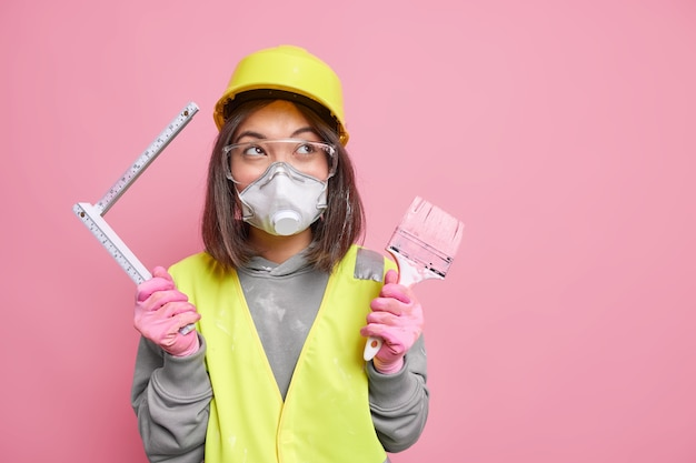 Woman wears safety glasses respirator and helmet holds painting brush tape measure repairs apartment stands