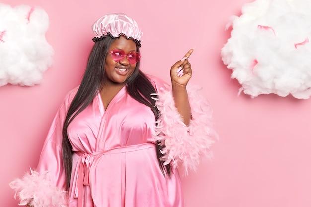 女性はシャワー キャップをかぶり、ガウンはピンクの白い雲のポーズを示します