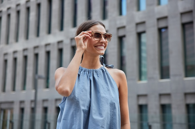 Woman wears stylish sunglasses blue dress looks away happily poses on blurred city building enjoys spare time