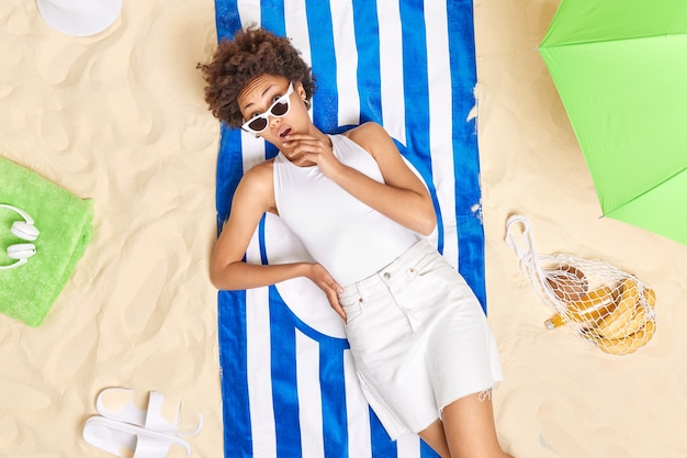Woman wears sunglasse white clothes lies on blue striped towel spends holidays at seaside surrounded by parasol bag of fruits slippers enjoys awesome summer day at beach