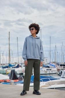 여자는 선글라스 후드티와 바지를 입고 요트 항구에서 포즈를 취하고 여가 시간을 즐깁니다.
