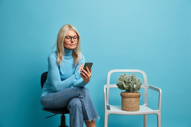 Woman wears transparent glasses neat clothes reads news online holds mobile phone while waiting in queue poses on chair alone isolated on blue