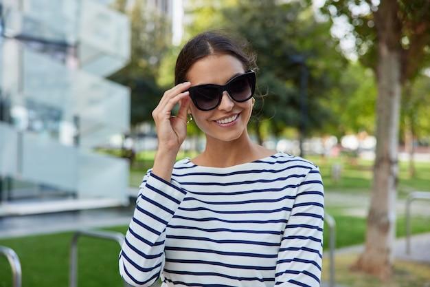 여자는 트렌디한 선글라스를 착용하고 공원을 걷습니다. 건물 정면을 통과합니다. 도시에서 자유 시간을 즐깁니다.