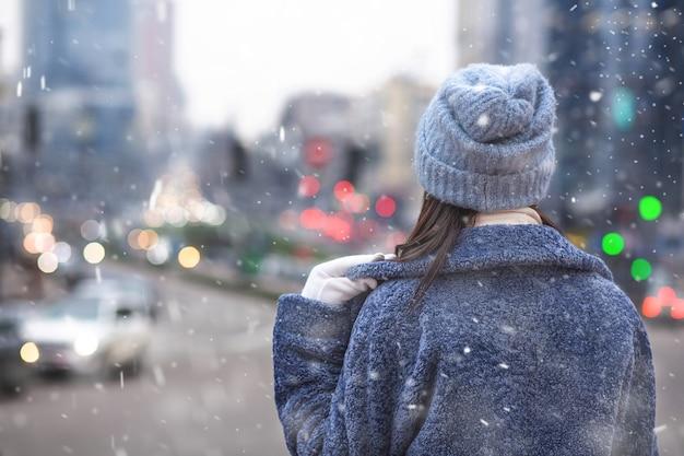 女性は雪の降る天気で街の交通を見ながら流行の冬のコートと帽子をかぶっています。テキスト用のスペース