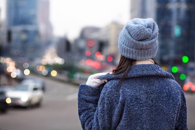 女性は夕方に街の交通を見て流行の冬のコートと帽子をかぶっています。テキスト用のスペース