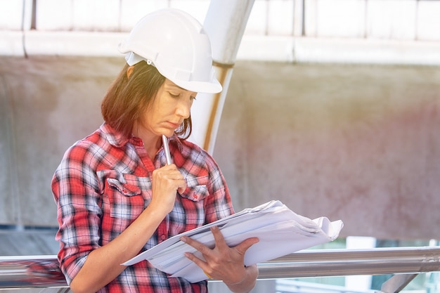 Woman wears white safety hat is working at construction site