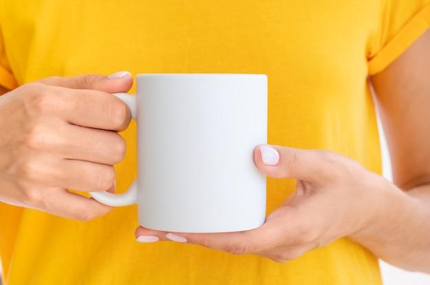 女性は暖かい一杯のコーヒーを保持している黄色のtシャツを着ています。ロゴのスペースをコピーします。
