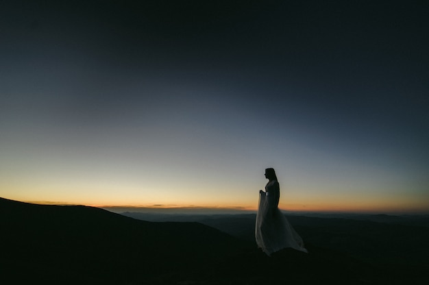 Woman in a wedding dress runs across the field toward the mountains