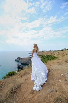 A woman in a wedding dress on top of a mountain on the n sea coast. girl with long blonde hair