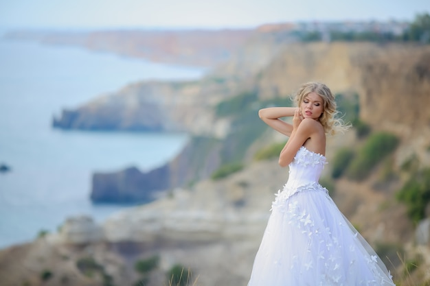 A woman in a wedding dress on top of a mountain on the sea coast. girl with long blonde hair