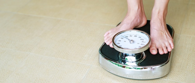 Woman weighing scales to control weight