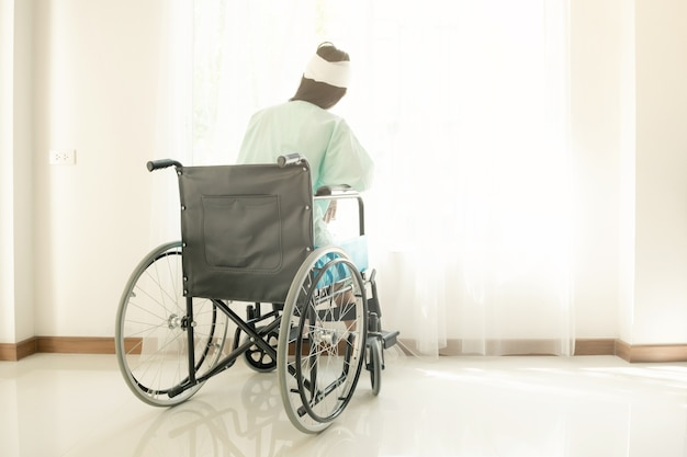 Woman in wheel chair looking out the window.