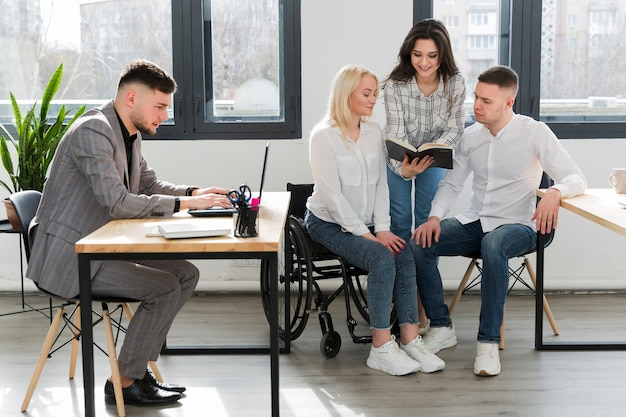Woman in wheelchair conversing with coworkers at office