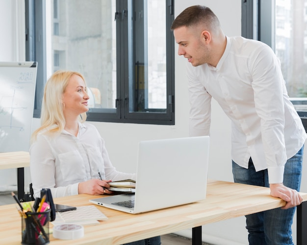 Woman in wheelchair conversing with make colleague